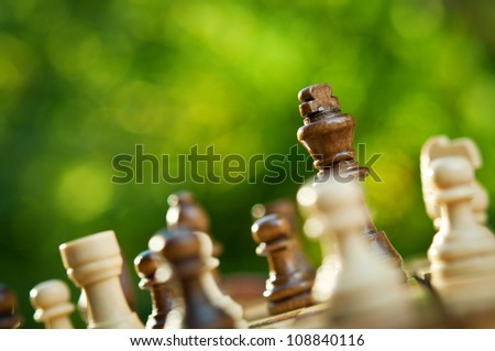chess pieces on a table in the park - stock photo