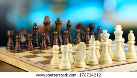 Chess pieces on board on bright background  - stock photo