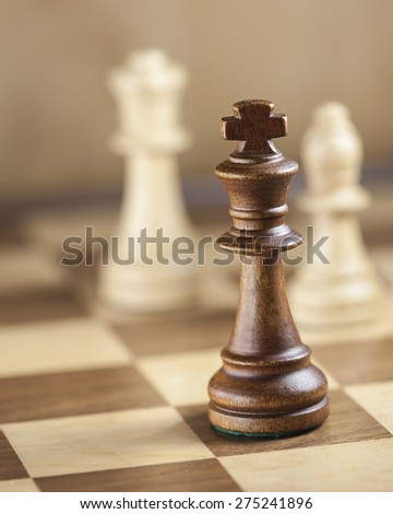 Chess pieces on game board background; focus on the king (shallow DOF) - stock photo