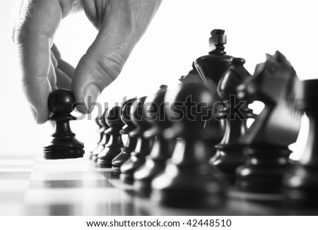 chess  player hand moves pawn selective focus black and white - stock photo