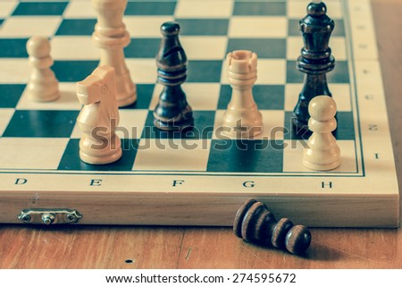 Chess set and chess pawn on wooden table, game and strategy concept, vintage photography. - stock photo