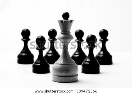 Chess white king and six black pawns on a white background in vintage