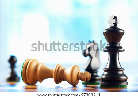 chess winner defeats white king abstract blue background - stock photo