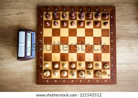 Chessboard with chess and clock, top view  - stock photo