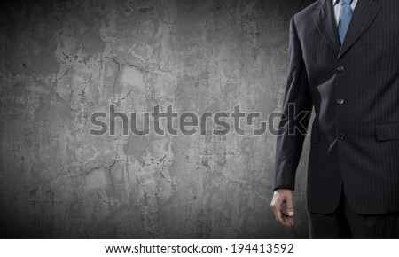 Chest view of businessman against cement wall - stock photo