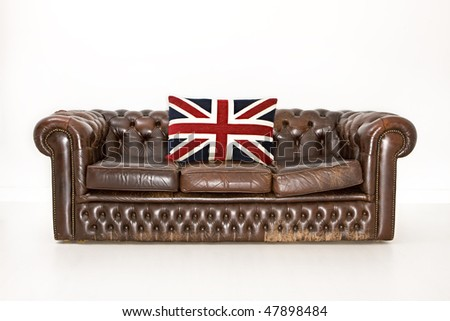Chesterfield couch with union jack cushion - stock photo