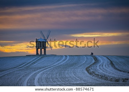 Chesterton windmill in snow at sunset - stock photo