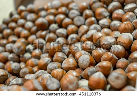 Chestnuts background, Chestnuts roasting. Many fresh tasty ripe sweet chestnut brown husks fruit edible seeds nuts full of vitamin for healthy eating for sale. Selective focus blurred background. - stock photo