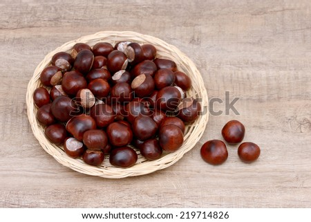 chestnuts lying in basket on wood - stock photo
