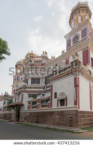 Chettinad, India - October 17, 2013: Chidambara Palace in Kadiapatti. Corner view on facade shows towers, balconies, balustrades, the front entrance, Krishna decorations. Mainly beige and purples - stock photo