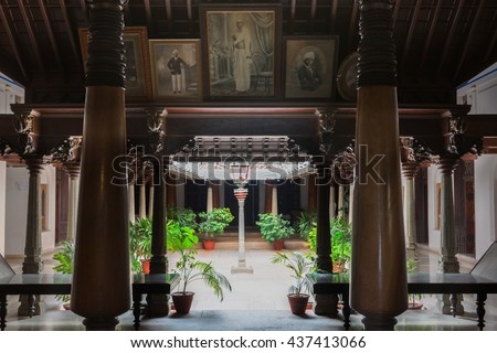 Chettinad, India - October 17, 2013: Chidambara Palace in Kadiapatti. Entrance hall leads to open air courtyard. Old sepia photos, green plants, dark brown wood. - stock photo