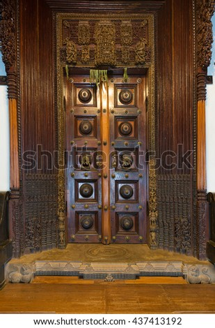 Chettinad, India - October 17, 2013: Chidambara Palace in Kadiapatti. Massive wooden dark brown antique door set in frame of hand chiseled wood. Mango leaves have spiritual and healing powers. - stock photo