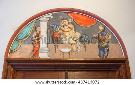Chettinad, India - October 17, 2013: Chidambara Palace in Kadiapatti. Wall painting above door showing Krishna playing flute while one woman plays the tabla instrument and another woman watches. - stock photo