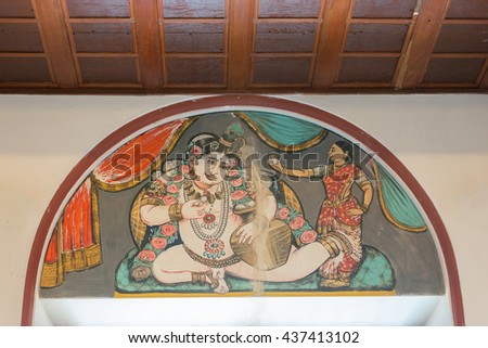 Chettinad, India - October 17, 2013: Chidambara Palace in Kadiapatti. Wall painting above door showing Krishna being offered butter by a woman. Crack in wall damaged painting. - stock photo