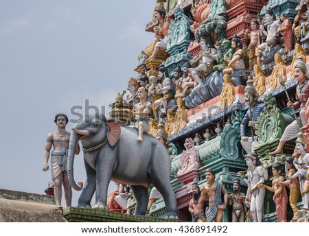 Chettinad, India - October 17, 2013:Detail of the Shiva temple gopuram at Kottaiyur shows Lord Shiva as supreme teacher and elephant walking away. Plenty of colorful statues. - stock photo