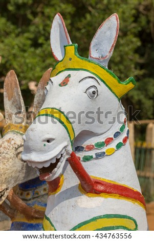 Chettinad, India - October 17, 2013: Kothamangalam Ayyanar horse shrine. Focus on the head of one laughing white horse with red, green and yellow trim.  - stock photo