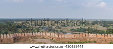 Chettinad, India - October 16, 2013: Panoramic view on the surrounding region of Thirumayam Fort. Ramparts and battlements in foreground. Battlements look like robot faces. - stock photo