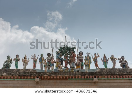 Chettinad, India - October 17, 2013: Row of statues shows the wedding of Shiva with Meenakshi and plenty of guests such as Vishnu, Ayyanar and Hayagriva. Against blue sky. - stock photo