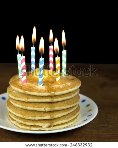 chevron birthday candles on a stack of breakfast pancakes - stock photo