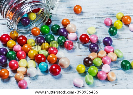 chewing gum and candies in jar on wooden background. focus on sweets and a glass jar - stock photo