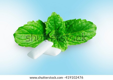 chewing gum with fresh mint leaves isolated on blue background - stock photo
