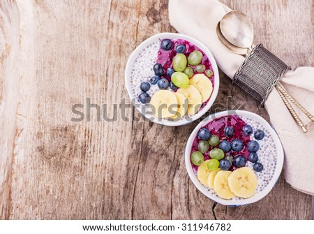 Chia Pudding for breakfast in bowls garnished with berry smoothies, grapes, petals of almond and blueberry in two portions on a wooden background with a napkin and spoon. Top view. selective Focus - stock photo