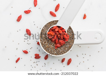 Chia seeds and goji berries on measuring spoons - stock photo