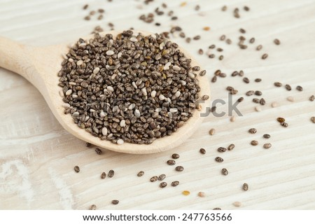 chia seeds in a spoon on wooden surface - stock photo