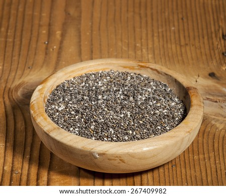Chia seeds in wooden bowl on wooden background.