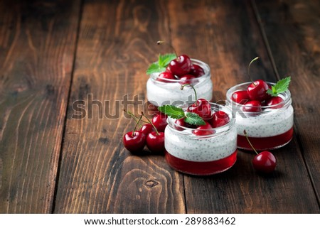 Chia seeds yogurt pudding, jelly and fresh sweet cherries in jar, selective focus - stock photo