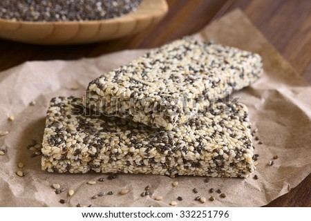Chia sesame honey granola bars, photographed with natural light. Chia (lat. Salvia hispanica) is considered a superfood (Selective Focus, Focus on the front edge of the granola bars) - stock photo