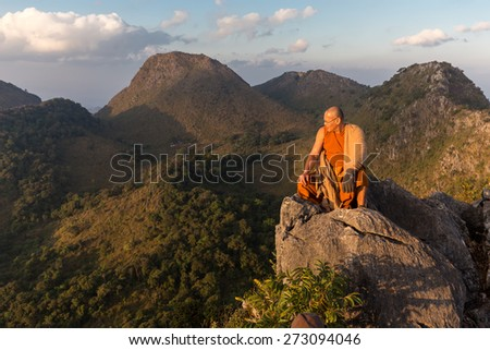 CHIANG DAO, THAILAND, JANUARY 05, 2015: A Buddhist monk master is meditating at the top of the Chiang Dao mount at dusk for the new year in Thailand. - stock photo
