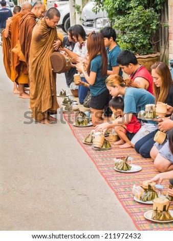 CHIANG KHAN, THAILAND - JUN 29, 2014 : Unidentified tourists offering sticky rice to Buddhist monk and Buddhist novice in the morning on June 29, 2014 at Chiang Khan, Loei, Thailand. - stock photo