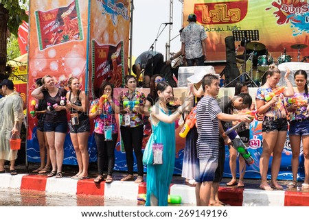 CHIANG MAI - APRIL 13 : A couple enjoy with splashing water in Songkran festival among crowd on the background at footpath around city's canal. on April 13,2015 in CHIANG MAI, THAILAND - stock photo