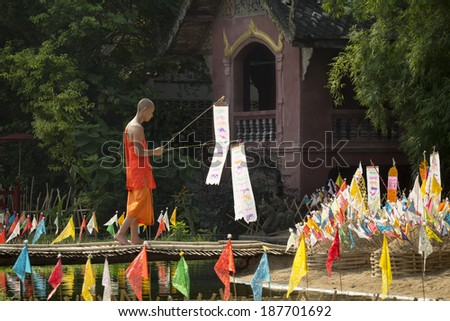 CHIANG MAI THAILAND - APRIL 17 : Songkran festival, Buddhist monk pin traditional flags on sand pagoda. APRIL 17,2014 in Phan-Tao Temple, Chiangmai, Thailand. - stock photo