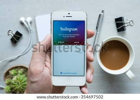 CHIANG MAI, THAILAND - DEC 20,2015: A man holds Apple iPhone with Instagram application on the screen. Instagram is a photo-sharing app for smartphones. - stock photo