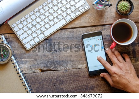 CHIANG MAI,THAILAND, DEC - 03 -2015 : A man pointing a iPhone 6 Space Gray with social networking service Google on the screen. iPhone 6 was created and developed by the Apple inc. - stock photo