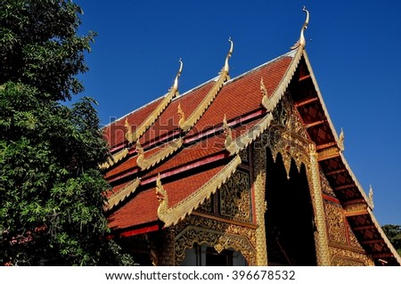 Chiang Mai, Thailand - December 19, 2012:  Gilded facade of the Ubosot hall with its gilded dragon figures on the roof and chofah ornaments at Wat Phra Singh
