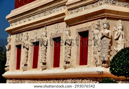 Chiang Mai, Thailand - December 19, 2012:  Thai khong figures with hands clasped in prayer decorate the base of the ancient Repository Library at Wat Phra Singh