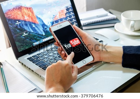 CHIANG MAI,THAILAND - FBE 21, 2016: Brand new Apple iPhone 6s plus with YouTube app on the screen lying on old wood desk with headphones. YouTube is the popular online video sharing website - stock photo