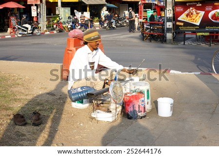CHIANG MAI, THAILAND - February 19, 2014: A street musician playing music with plastic buckets in Chiang mai, Thailand. - stock photo