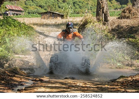 CHIANG MAI, THAILAND - FEBRUARY 8 : Tourists riding ATV to nature adventure on dirt track on FEBRUARY 8, 2014 in Chiang Mai, Thailand. - stock photo