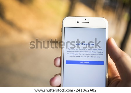 CHIANG MAI, THAILAND - JANUARY 04, 2015: A man trying to join to Facebook application using Apple iPhone 6. Facebook is largest and most popular social networking site in the world. - stock photo