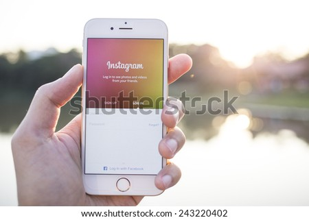 CHIANG MAI, THAILAND - JANUARY 02, 2015: A man trying to log in Instagram application using Apple iPhone 6. Instagram is largest and most popular photograph social networking site in the world. - stock photo