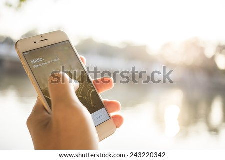 CHIANG MAI, THAILAND - JANUARY 04, 2015: A man trying to log in Twitter application using Apple iPhone 6. Twitter is largest and most popular social networking site in the world. - stock photo