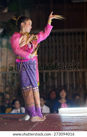 CHIANG MAI, THAILAND, JANUARY 04, 2015: A woman is performing a Thai traditional dance at an outdoor stage during the Saturday night street market in Chiang Mai, Thailand - stock photo