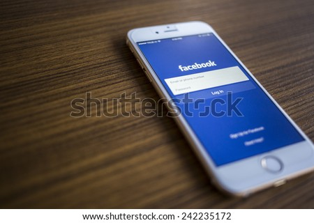 CHIANG MAI, THAILAND - JANUARY 02, 2015: Facebook Login page application on  Apple iPhone 6 and wood background. Facebook is largest and most popular social networking site in the world. - stock photo