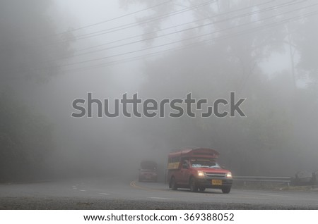 CHIANG MAI, THAILAND - JANUARY 27: So much mist on the road to Doi Suthep on January 27, 2016 in Chiang Mai. Public transportation car of Chiang Mai  in the mist at Doi Suthep road.
