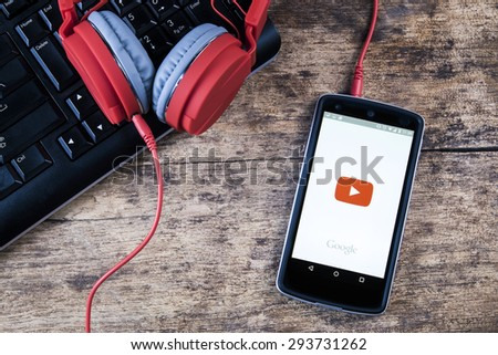 CHIANG MAI, THAILAND -JULY 5, 2015:LG Nexus 5 open YouTube app on the screen lying on desk with headphones. YouTube is the popular online video-sharing website. - stock photo