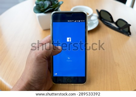 CHIANG MAI ,THAILAND - JUNE 22, 2015: Young man handle IPHONE 6 PLUS. Facebook is largest and most popular social networking site in the world.  - stock photo